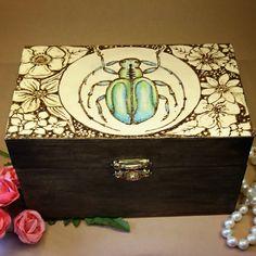 Angegebene Preise sind Gesamtpreise. Umsatzsteuer gem. § 19 UStG nicht ausgewiesen.  In Brandmaltechnik verziertes Holzkästchen für Schmuck oder die Aufbewahrung anderer Kostbarkeiten. Blumen und ein türkis-grün schillernder Käfer zieren diese kleine Schatztruhe in den Maßen 15x10x8 cm. Innen und Wood Colors, Colours, Rustic Feel, Brass Color, Treasure Chest, Messing, Painting Techniques, Wooden Boxes, Iridescent