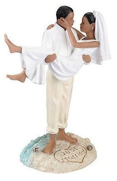 """Made of hand painted resin, this beach couple figurine measures 7"""" tall. The widest point is 5"""" and the base measures 3.75"""" wide. The groom lovingly carries his bride in the sand, which has been decor"""