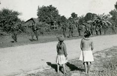 Column from the 2nd battalion of WWII's 475th Regiment are watched by two young girls as they march through a village in Burma.  Photographer Quaid