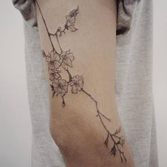 Fine line style cherry blossom tattoo on the right arm. Tattoo artist: Doy.