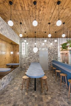 sans arc studio used blue terrazzo grey travertine and stained wood to evoke a subtle sea side experience for diners at this adelaide chip shop
