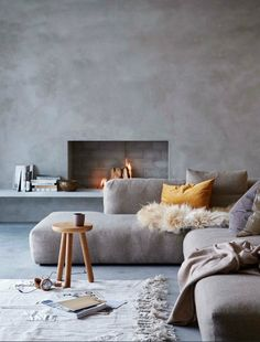 A minimal living room all in gray with a fireplace. The walls and floor are in gray microcement. There are several throw pillows on the gray sectional sofa, a wooden stool besides with a mug on it, magazines on the floor and timber logs burning in the fireplace.