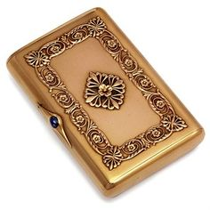 A Jewelled Gold Cigarette Case  by Fabergé, with the workmaster's mark of Gabriel Niukkanen, St Petersburg, 1899-1904 Rectangular with rounded corners, the hinged cover applied with a rosette of anthemions centring a flower-head, within a border of acanthus leaves and flowerheads with anthemions at the corners, with cabochon sapphire thumb-piece, marked inside cover and base, also with scratched number 2083D
