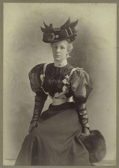 1890s portrait of a woman in a gorgeous dress, hat, and muff. Look at that tiny waist!