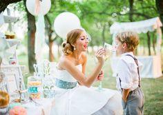 Braut im kurzen 50er Jahre Hochzeitskleid mit blaugrünem Gürtel mit bunten Punkten, Fascinator mit kleinen Blümchen in ivory und süßem Blumenkind mit Hosenträgern vor der Candy Bar