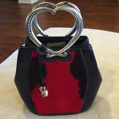 """Brighton leather and pony hair  mini bag Brighton small handbag with silver tone handles and black leather with black and red pony hair inset on front.  The bag is 7"""" long x 8"""" wide and 3 1/2"""" deep.  There is a snap enclosure at the top and the two heart handles are 3"""" long x 4"""" wide and show the only wear on this bag 5)243 is some tarnish on the handles.  It's an adorable little, whimsical bag. Brighton Bags Mini Bags"""