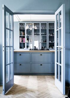French kitchen with wood floors, blue doors, and blue cabinents