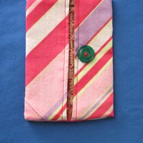Keep your tissues from getting squished in your bag with this handy tissue holder. This item snuggly holds standard size to-go tissue packets  Pink stripe print fabric on the outside and multi  pink cotton fabric on this inside with green button accent