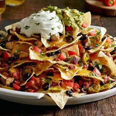 Holy guacamole, are these nachos good! An expert nacho-stacking technique leaves no chip un-cheesed—so everyone gets a taste of this epic stack. The best part? You can add whatever you want…prefer steak to chicken? You got it. Like fresh jalapenos? Use those instead of the pickled kind. Plus, homemade guac. There's nothing better to please a crowd.