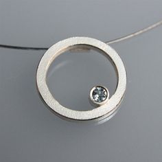 This minimalistic contemporary pendant is made in sterling silver and has a 3mm blue topaz.    The pendant is made of 2mm square wire in silver