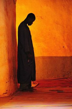 Photograph by Lawrence Smith    A brief encounter with a person in a dimly lit mosque in the country of Mali shows a man deep in prayer. I tried to capture the moment without disturbing the person