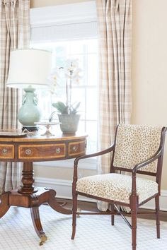 Inlaid mahogany rent table with celadon green lamp and Regency arm chair upholstered in Cowtan & Tout beige  animal print fabric