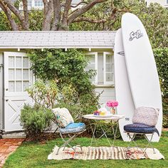 Backyard shed with stand-up paddleboards and bistro table and chairs at Kelly Sawyer Patricof's Breezy Malibu Beach Cottage