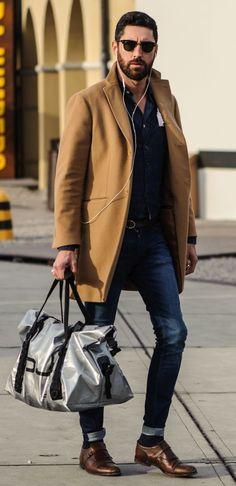 Shop this look on Lookastic:  https://lookastic.com/men/looks/overcoat-waistcoat-denim-shirt/14299  — Dark Brown Sunglasses  — Navy Denim Shirt  — Navy Denim Waistcoat  — Dark Brown Leather Belt  — Camel Overcoat  — Navy Skinny Jeans  — Grey Canvas Duffle Bag  — Dark Brown Leather Monks