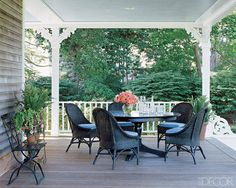 THE COMFORT FACTOR SJP weekend home On the front porch, wicker chairs surround an Aris pedestal table from Pottery Barn; the ceiling is painted with Benjamin Moore's Hazy Blue.