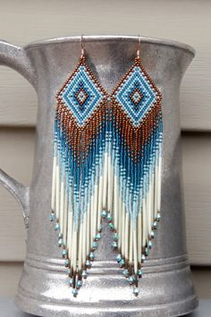 Hand-beaded with the smallest beads available, these unique earrings are done in dark copper, light blue/aqua and deep teal blue colors. The fringe includes authentic porcupine quill in their natural color and aurora borealis turquoise bicone Swarovski crystals for the perfect, eye-catching sparkle. These earrings are 5 3/4 in length, including the rose-gold ear-wires, and just a bit over an inch wide. I used brick (also called a Cheyenne) stitch to create them. They are ready to ship - rush…