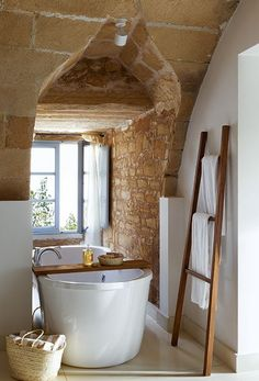 Love the rock wall, the old ladder used as a towel rack, and the wonderful little tub.
