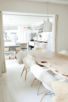 All white kitchen and dining. The sheepskin chair covers are a warm and inviting decor idea. Home Decor Salle à manger