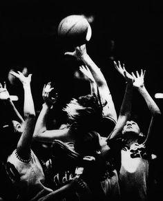 Photographer/Creator  Bob Modersohn  Collection  1974  Publisher  Des Moines Register & Tribune  Caption/Description  Photographer says, 'Joyce Elder drives for basket through flame of hands during Iowa Girls State Basketball Tourney.'