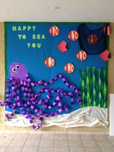 inside fish bulletin board add octopus and seaweed kids names on the fish write We're Happy to Sea You