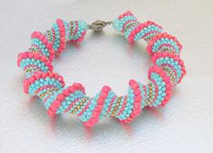 A teal and red cellini spiral bracelet that has a southwestern feel. All the seed beads in this bracelet are matte and it gives it a unique look and feel. Bring out your boho/artsy side with this bracelet that will go with a skirt or jeans. Wear it alone or stack it with other bracelets. It fits a 7 1/2 wrist. Brass snap clasp. Treat yourself