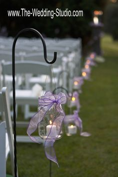 Ball mason jar decorated this outdoor ceremony with simplistic beauty. Purple ribbons tied around jars with a white votive candle. Lots of compliments from the guests! The Wedding Studio, Schaumburg IL