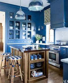 In a Maine family complex designed by Suzanne Kasler and architect Les Cole, the poolhouse kitchen features Urban Archaeology pendant lights, a Thermador range, and counter stools from Walters | http://archdigest.com