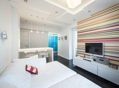 weißes Wohnzimmer mit angrenzender Küche und bunt gestreifter Akzentwand