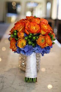 two toned circus roses, orange ranunculus, lush blue hydrangea and green hypericum berries