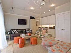 living rooms - family room with wet bar, wet bar in living room, built in bar area, taupe and orange paisley floor pillows, paisley floor pillow, orange and gray paisley ottoman, round button tufted stools, orange pleated stool, orange garden stool, distressed square coffee