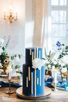 Umwerfende Hochzeitstorte in Blau und Gold mit einer Rose dekoriert. Schlichtes Design und klare Linien unterstreichen diesen Hingucker.