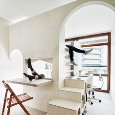 London-based architects Studio Ben Allen has built this plywood structure inside a flat in London's brutalist Barbican Estate to create a bedroom for two children, featuring archways, steps and a fold-down desk.