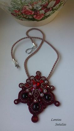 Beautiful handmade soutache pendant. Materials: soutache ribbon, Garnet stone, crystal Swarovski, glass beads. Strips length – 45 cm., pendant length – 8 cm. Sturdy metal clasp. Back - natural leather.