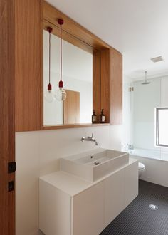Wooden joinery offers a warm contrast to the white surfaces in this bathroom.