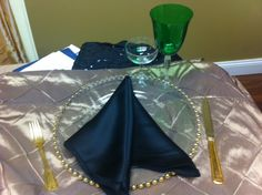 gold pin tuck, black satin napkin, green wine glass, coup champagne glass