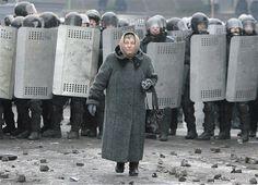 Jan. 22, 2014: An elderly woman walks away from riot police as they block a street during unrest in Kiev, Ukraine.