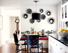 """Varney created a """"young and snappy"""" kitchen by Draperizing it in black and white. Walls pained Benjamin Moore's Decorator's White set off by Unity and Embrace baskets made in Rwanda from macys.com. The table was made by H.J. Martin and Son. Catalina chairs from Ficks Reed. Through the doorway is an African wall-hanging"""