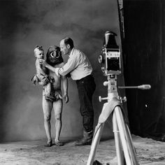 Photographer Irving Penn. Photograph by Lisa Fonssagrives-Penn. He is shown here photographing a New Guinea mud man and a child