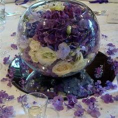 deep purple hydrangeas, deep purple lisianthus and ivory Avalanche roses, tightly packed within a large fish bowl vase