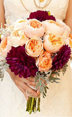 Soft peach ranunculus are accented by deep ruby dahlias in this exotic bouquet.