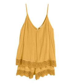 Sleeveless jumpsuit in woven, crêped fabric with lace details. V-neck at front and back, narrow shoulder straps, elasticized seam at waist, and short, wide-cut legs. Opening at back with button at back of neck. Lace trim at hems and at hem of top section.