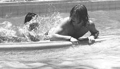 """John Bonham and Robert Plant in a pool in Honolulu, 1969.   """"Bonham and Plant fought over the use of a surfboard. Bonham ended up losing the surfboard but he got back at Plant by yanking his trunks off."""" - Robert Knight"""