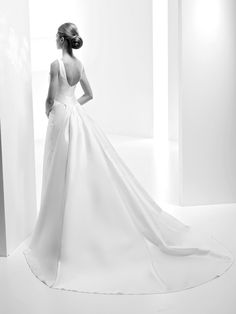 Chamira- This beautiful classic design displays a large train that begins at the back, contrasting with its bateau bodice and round back. A dress made completely from Mikado, a fabric that gives volume and accentuates the femininity of its wearer.