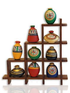 This ethnic wall art piece is a modern take to warli art where the artisans have used vegetable colors to paint on the clay pots; these pots are then put together in a wooden frame representing a hut/house which makes for a fresh colorful art form to adorn your walls.  Warli Art dates back to 2500 - 3000 BC was discovered on the state borders of Maharashtra and Gujurat. Practised mostly by the tribal people of the area (adivasis) this art tells a story using primarily three symbols…