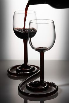 """MY OTHER HALF by Jim Rokos.   A pair of wine glasses, which allows the liquid to flow freely between the two glasses. Because liquid finds it's own level, it flows down to the lowest glass. Users must learn to cooperate, to drink their wine.   """"I like the idea of being able to reward people for good behaviour...""""   Psychologist - John Kentish.  Hand made by Jochen Holz.  Photograph by Carlo Draisci."""
