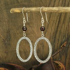 Handmade 925 Sterling Silver and genuine Garnet gemstone dangle earrings. A 6 mm Garnet gemstone faceted bead is set on top of the oval shaped solid
