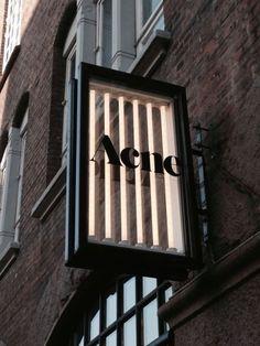 Acne signage: layered illuminated glass box with black frame shop signage, retail signage, Shop Signage, Retail Signage, Wayfinding Signage, Signage Design, Environmental Graphics, Environmental Design, Habitat Collectif, Led Neon, Blade Sign