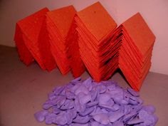 Orange plantable place cards and purple heart shped seed bombs for wedding favors