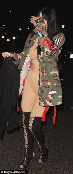 Blending in? The reality star teamed a nude crop top and matching leggings with an oversized camouflage jacket and thigh-high lace-up boots for her night out