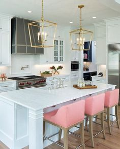 Pink chairs, white cabinets, and marble counter tops.